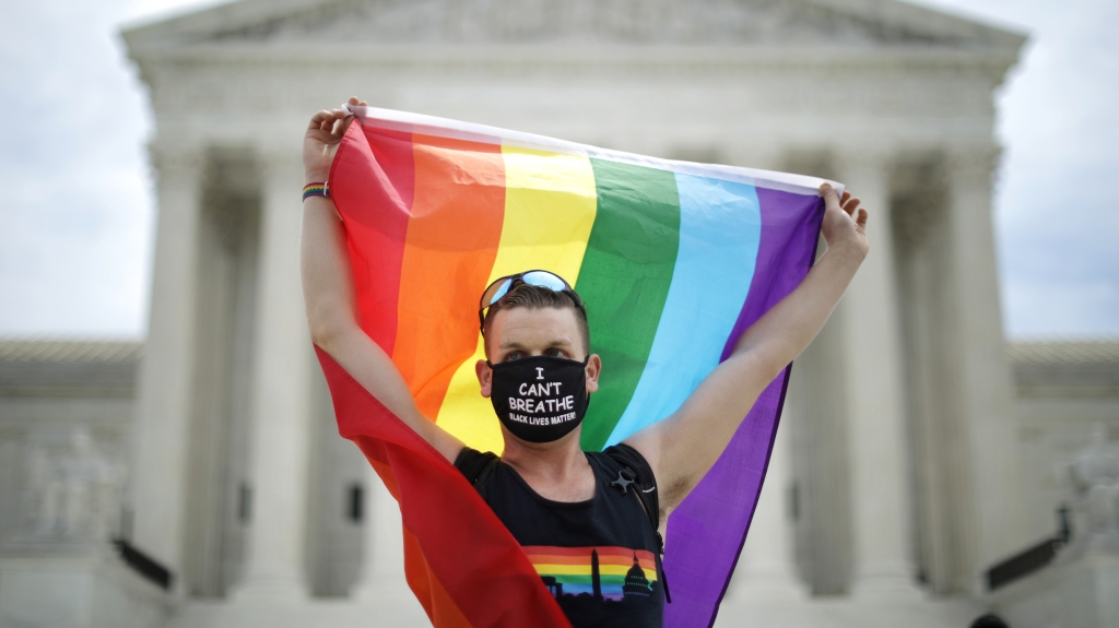 Joseph Fons holds a Pride flag in front of the U.S. Supreme Court building after the court ruled that LGBTQ people can not be disciplined or fired based on their sexual orientation June 15, 2020 in Washington, D.C.