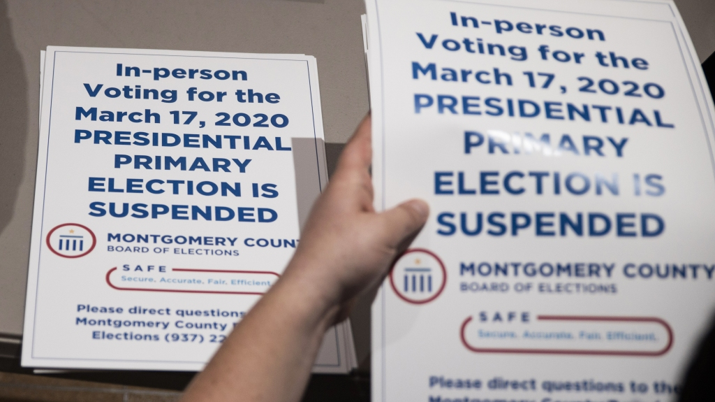 County election workers hand out election delayed signs to put up at polling stations in Dayton, Ohio on March 17, 2020 after the primaries were canceled due to the coronavirus.