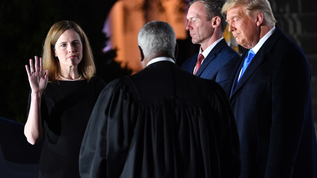Supreme Court Associate Justice Clarence Thomas swears in Amy Coney Barrett as a U.S. Supreme Court Associate Justice, flanked by her husband Jesse M. Barrett, during a ceremony on the South Lawn of the White House, Oct. 26, 2020, in Washington, D.C.