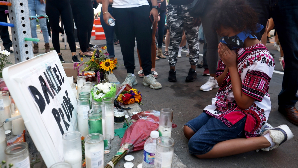 """Hasan Massey Jr., 11, kneels in prayer at a make-shift memorial at the site where Daniel Prude was arrested on Sept. 3, 2020, in Rochester, New York. Prude died after being arrested by Rochester police officers who had placed a """"spit hood"""" over his head and pinned him to the ground while restraining him."""