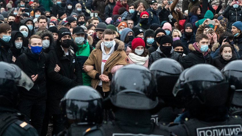 In this Jan. 23, 2021, file photo, people stand in front of police officers during a protest against the jailing of opposition leader Alexei Navalny in Moscow, Russia.