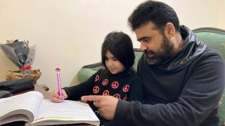 Syrian refugee Mahmoud Mansour, 47, helps his youngest daughter Sahar, 8, with her homework at his rented apartment in Amman, Jordan, Wednesday, Jan. 20, 2021. President Joe Biden has vowed to restore America's place as a world leader in offering sanctuary to the oppressed by raising the cap on the number of refugees allowed in each year. Mansour's family had completed the work to go to the United States when the Trump administration issued its travel ban barring people from Syria indefinitely and suspending the refugee program for 120 days.