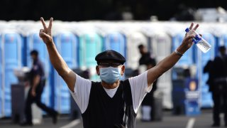 A person wearing a protective mask gestures after receiving a dose of Covid-19 vaccine.