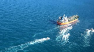 """In this photo released Monday, Jan. 4, 2021, by Tasnim News Agency, the MT Hankuk Chemi, a South Korean-flagged tanker is escorted by Iranian Revolutionary Guard boats on the Persian Gulf. Iranian state television acknowledged that Tehran seized the oil tanker in the Strait of Hormuz. The report on Monday alleged the MT Hankuk Chemi had been stopped by Iranian authorities over alleged """"oil pollution"""" in the Persian Gulf and the strait."""