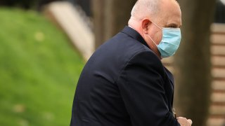 Governor Larry Hogan walks away from the camera to the right wearing a mask and blazer