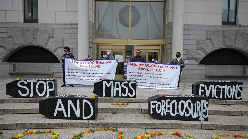 Demonstrators display signs calling for an end to evictions and foreclosures during a rally at Boston Housing Court outside the Edward W. Brooke Courthouse in Boston on Oct. 29, 2020.