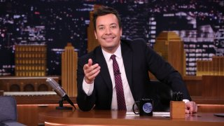 """In this Nov. 16, 2018, file photo, host Jimmy Fallon sits at his desk on the set of """"The Tonight Show Starring Jimmy Fallon."""""""
