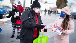 Community health workers with CASA de Maryland hand out brochures with coronavirus information to people lining up at a food distribution site behind Clifton Park Baptist Church in Silver Spring, MD. As vaccinations continue, local governments and commun
