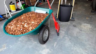 This image provided by Olivia Oxley shows a wheelbarrow filled with pennies, March 20, 2021 in Fayetteville, Ga. A Georgia man said his former employer owed him a pretty penny, $915 to be exact, after leaving his job in November. But Andreas Flaten said he was shocked to see his final payment: 90,000 oil or grease covered pennies, at the end of his driveway earlier this month, news outlets reported. Atop the pile was an envelope with Flaten's final paystub and an explicit parting message.