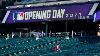 A worker cleans seats to prepare Coors Field for the return of fans in the era of the coronavirus during a news conference Wednesday, March 31, 2021, at the stadium in downtown Denver. A small number of fans were allowed to watch the Rockies go through a workout Wednesday before the team hosts the Los Angeles Dodgers in the squads' season-opener Thursday, April 1.