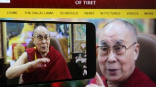In this photo illustration the Tibetan spiritual leader the Dalai Lama is seen on a mobile phone screen during a live webcast of his talk show on Educating the Heart by video link at his residence in Dharamsala, India.