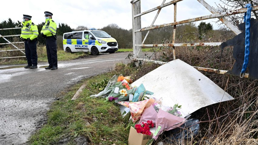 Flowers and messages of condolence for Sarah Everard are seen as police officers patrol near the woodland where police officers found human remains near Ashford, southeast England, on March 12, 2021, - A body found hidden in woodland in Kent has been identified as that of Sarah Everard. Metropolitan Police Assistant Commissioner Nick Ephgrave announced outside Scotland Yard on March 12, 2021, that the body found hidden in woodland in Kent has been identified as that of Sarah Everard.