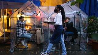 People sitting inside plastic tents at an outdoor cafe with a waitress wearing a face mask carrying a serving tray.