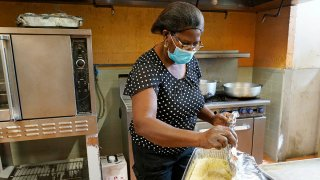 Doramise Moreau covers shredded malanga that will be served with baked fish to those that need a meal at Notre Dame d'Haiti Catholic Church, March 8, 2021, in Miami.