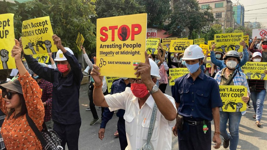 Anti-coup protesters display signs and shout slogans as they protest against the military coup in Mandalay, Myanmar, Monday, March 15, 2021. Myanmar's ruling junta has declared martial law in parts of the country's largest city as security forces killed more protesters in an increasingly lethal crackdown on resistance to last month's military coup.