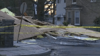 Piles of what appear to be plywood and other debris fills a side street, cordoned off by yellow tape.