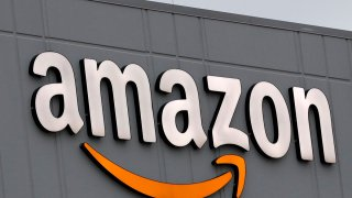 A sign is lit on the facade of an Amazon fulfillment center, Thursday, March 19, 2020, on Staten Island in New York.