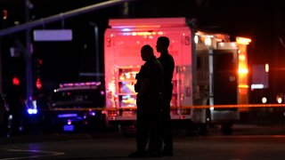 Two police officers stand outside an office building where a shooting occurred in Orange, Calif., March 31, 2021. The shooting killed several people, including a child, and injured another person before police shot the suspect, police said.