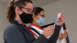 People prepare Covid-19 vaccines at an old TJ Maxx store