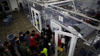 Minors talk to an agent outside a pod at the Department of Homeland Security holding facility run by the Customs and Border Patrol (CBP) on March 30, 2021 in Donna, Texas.
