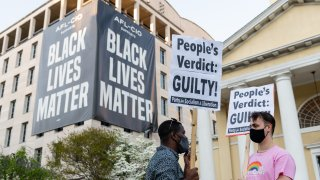 People carry signs after the verdict is announced in the trial of former Minneapolis police officer Derek Chauvin in Black Lives Matter Plaza in Washington, D.C., U.S., on April 20, 2021. Former Minneapolis police officer Derek Chauvin was found guilty of killing George Floyd when he knelt on the mans neck for 9 minutes and 29 seconds, a videotaped death that ignited a summer of rage and the greatest racial reckoning in the U.S. since the 1960s.