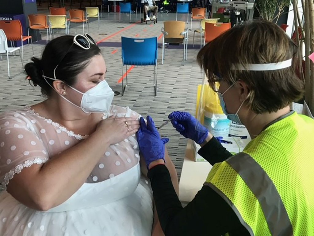 Sarah Studley gets a vaccination wearing the gown she planned to wear to her wedding reception.