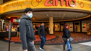 People wear face masks as they walk by a movie theater during the coronavirus disease (COVID-19) pandemic in Newport, New Jersey, April 2, 2021.