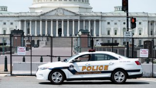 In this April 28, 2021, file photo, a U.S. Capitol Police patrol car drives past the fence perimeter on the east side of the U.S. Capitol before President Joe Biden delivers his address to the joint session of Congress.