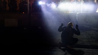 police shine lights on a demonstrator with raised hands during a protest outside the Brooklyn Center Police Department on in Brooklyn Center, Minn.