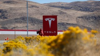 FILE - In this Oct. 13, 2018, file photo, a sign marks the entrance to the Tesla Gigafactory in Sparks, Nev. Egor Kriuchkov, a Russian citizen accused of offering a Tesla employee $1 million to enable a ransomware attack at the electric car company's plant in Nevada, pleaded not guilty Thursday, Sept. 24, 2020, to a federal conspiracy charge.