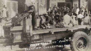 This photo provided by the Department of Special Collections, McFarlin Library, The University of Tulsa shows a truck parked in front of the Convention Hall with a Black man whose condition is unknown lying on the bed of a truck during the Tulsa Race Massacre in Tulsa, Okla