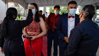 Grace Gardens Event Center employees check temperatures of young people attending prom at the Grace Gardens Event Center in El Paso, Texas, on May 7, 2021. Around 2,000 attended the outdoor event at the private venue after local school districts announced they would not host proms this year.