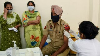 A medical worker inoculates a policeman with a dose of the Covishield coronavirus vaccine at a civil hospital in Amritsar on May 1, 2021 during the first day of India's vaccination drive to all adults.