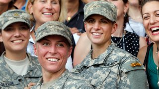 Army 1st Lt. Shaye Haver, center, and Capt. Kristen Griest, right, pose for photos with other female West Point alumni after an Army Ranger school graduation ceremony