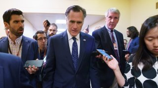 Sen. Mitt Romney, R-Utah, is surrounded by reporters as he walks to the Senate chamber for votes, at the Capitol in Washington, Thursday, June 10, 2021. Sen. Romney is working with a bipartisan group of 10 senators negotiating an infrastructure deal with President Joe Biden.