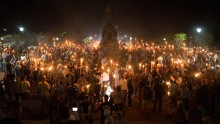 Members of the alt-right and white supremacist groups encircle counter-protestors at the base of a statue of Thomas Jefferson after marching through the University of Virginia campus with torches in Charlottesville, Va., on Aug. 11, 2017.