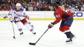 Washington Capitals left wing Shane Gersich (63) skates with the puck during his first NHL game in front of New York Rangers center Lias Andersson (50) during the first period at Capital One Arena.