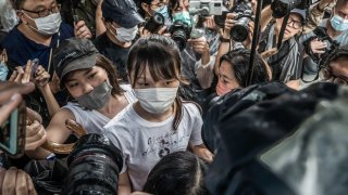 Agnes Chow (C) walks through the media pack after being released from the Tai Lam Correctional Institution.