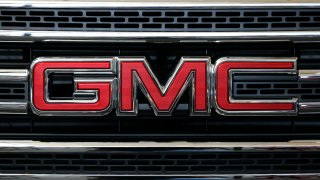 A closeup of the GMC logo on a car's grill.