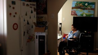 Francisca Perez, 84, sits by the dining table on a wheelchair in her house in Chicago's Little Village neighborhood