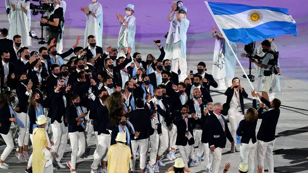 Cecilia Carranza Saroli and Santiago Raul Lange, of Argentina, right, carry their country's flag during the opening ceremony in the Olympic Stadium as Team Argentina sings at the 2020 Summer Olympics, Friday, July 23, 2021, in Tokyo, Japan.