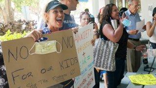 Joann Marcus of Fort Lauderdale, left, cheers as she listens to the Broward School Board's emergency meeting