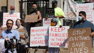 People from a coalition of housing justice groups hold signs protesting evictions