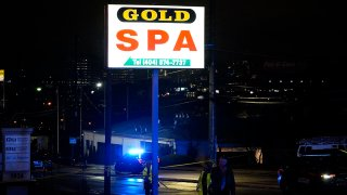 FILE - Officials in front of Gold Spa after a deadly shooting on March 16, 2021, in Atlanta.