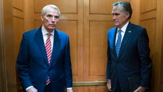Sen. Rob Portman, R-Ohio, left, accompanied by Sen. Mitt Romney, R-Utah, leave in the elevator after closed door talks about infrastructure on Capitol Hill in Washington, July 15, 2021.