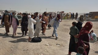Stranded people gather and wait to open the border which was closed by authorities, in Chaman, Pakistan