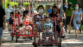 Adults and children ride pedal cycles