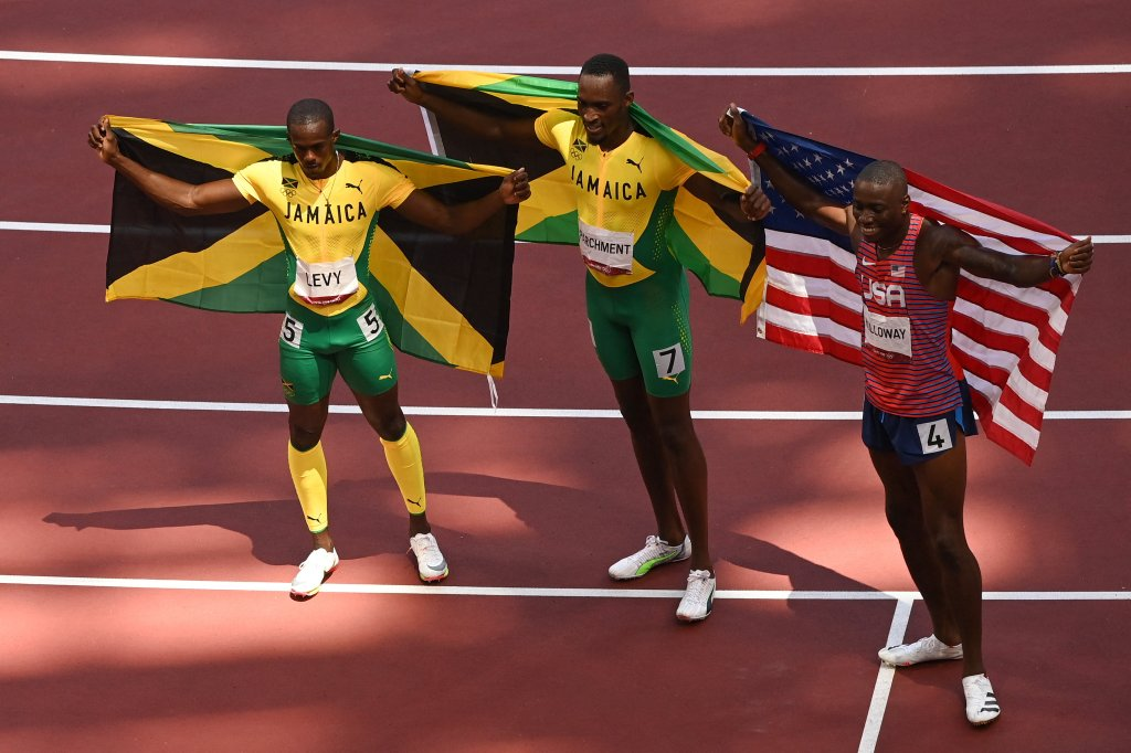 (From L) Third-placed Jamaica's Ronald Levy, first-placed Jamaica's Hansle Parchment and second-placed USA's Grant Holloway celebrate after competing in the men's 110m hurdles final during the Tokyo 2020 Olympic Games at the Olympic stadium in Tokyo on August 5, 2021.