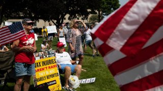 Demonstrators gather with flags and signs to protest against mandated vaccines outside of the Michigan State Capitol on August 6, 2021 in Lansing, Michigan.