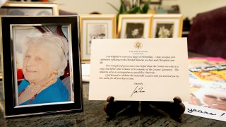 A note from President Joe Biden is seen placed among photos of Primetta Giacopini, who died of COVID-19 11 days prior in Richmond, Calif. on Monday, Sept 27, 2021. Primetta Giacopini's life ended the way it began — in a pandemic. She was two years old when she lost her mother to the Spanish flu in Connecticut in 1918. Giacopini contracted COVID-19 earlier this month. The 105-year-old struggled with the disease for a week before she died Sept. 16.